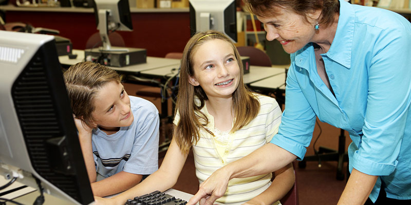 A librarian assisting children with library computers