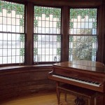 A vintage piano and stained glass windows inside Thistle Cottage.